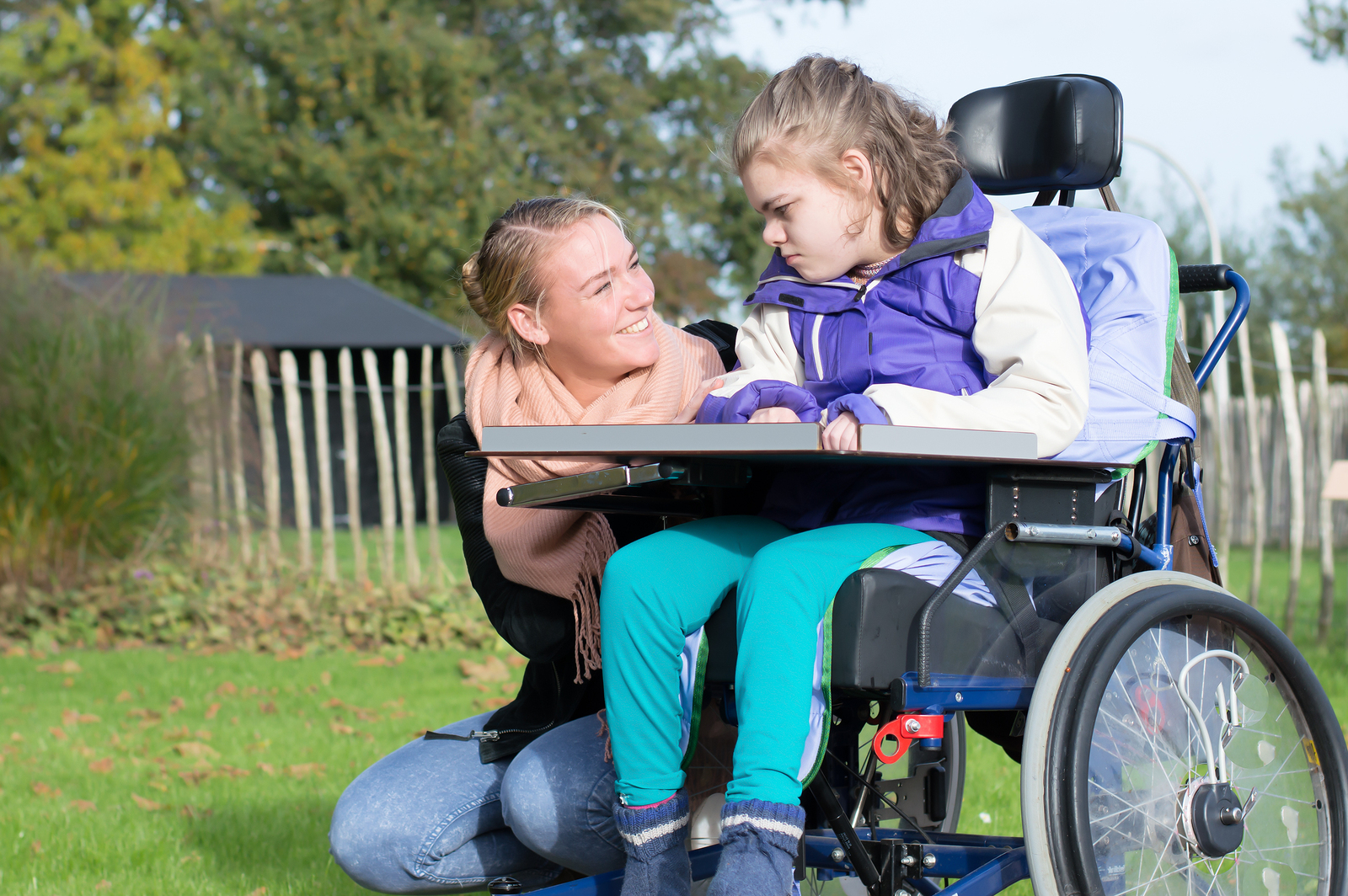 Disability a disabled child in a wheelchair relaxing outside together with a carer