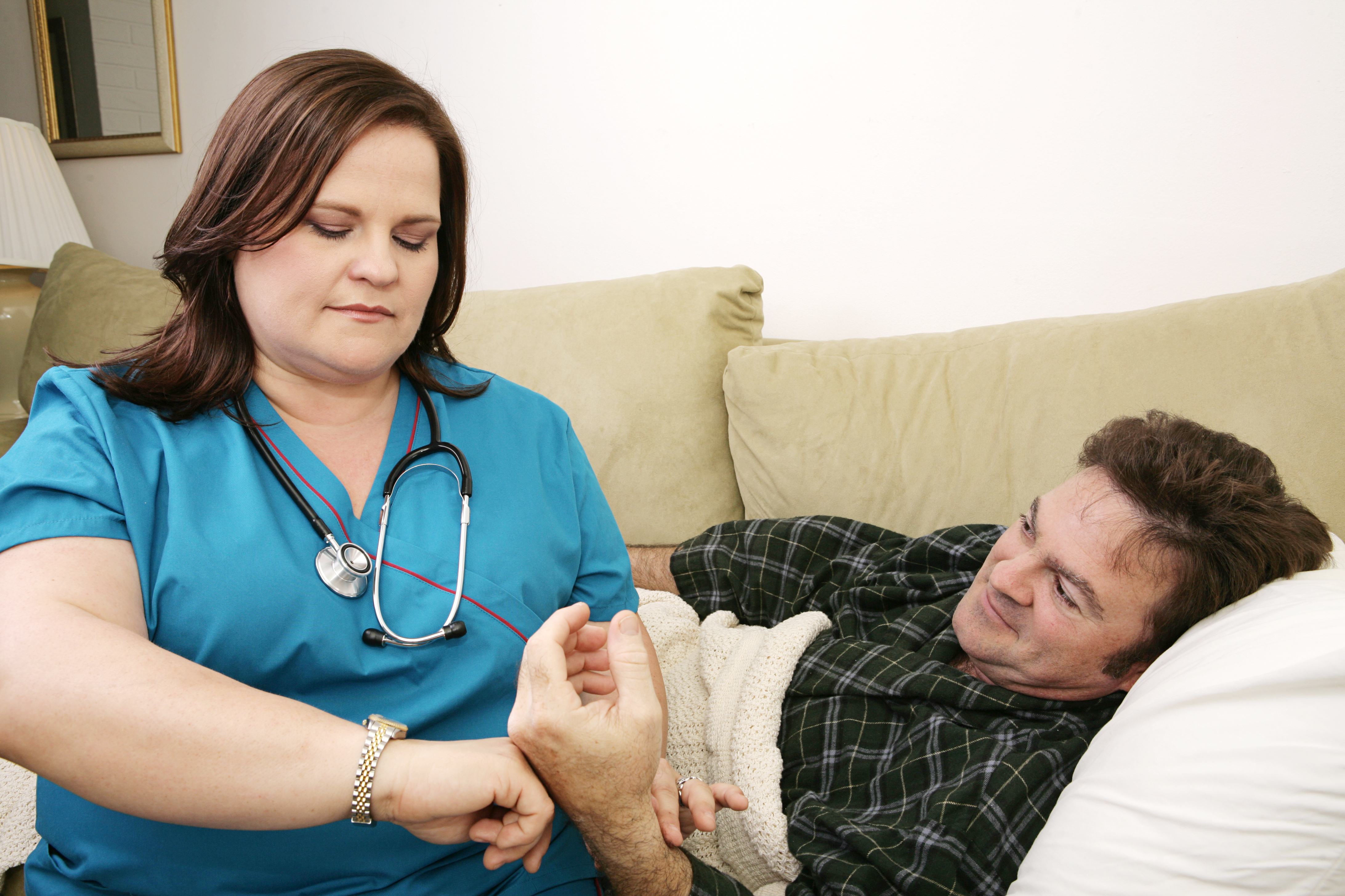 A home health nurse taking the patient's pulse.